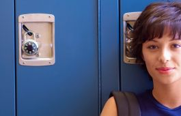 Girl standing in front of lockers with backpack